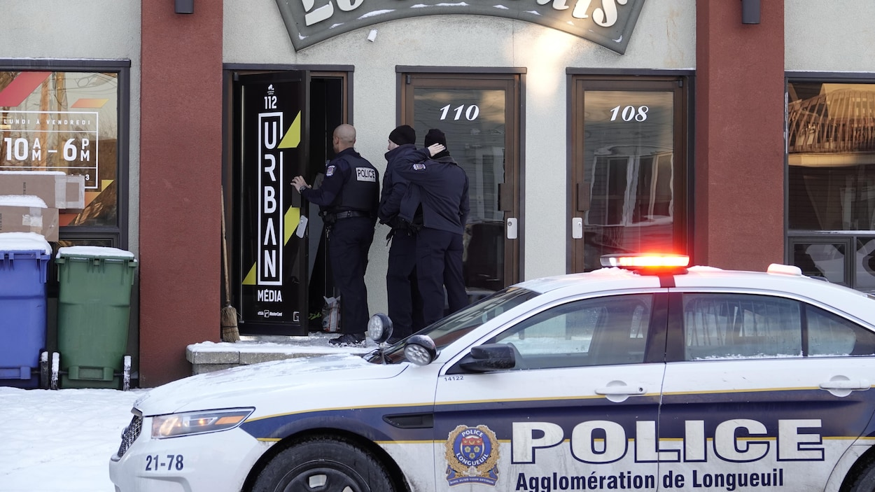 Trois policiers entrent dans un commerce.