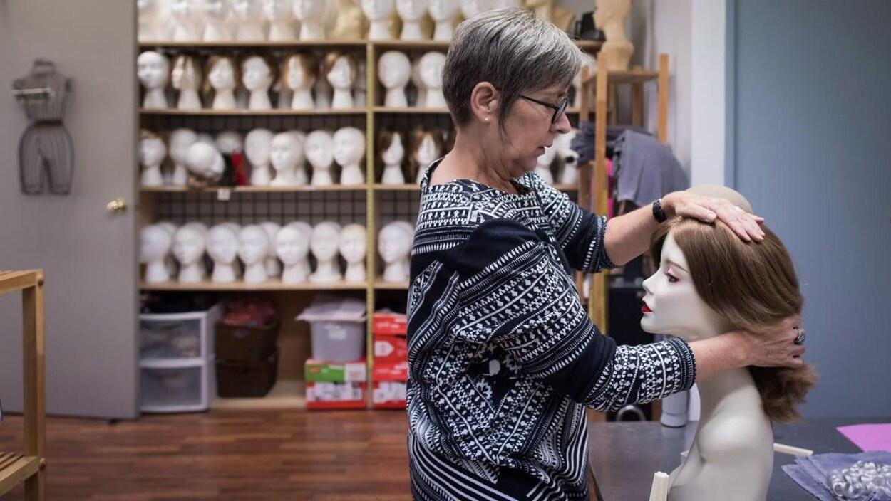Une femme de profil pose une perruque sur une tête de mannequin.