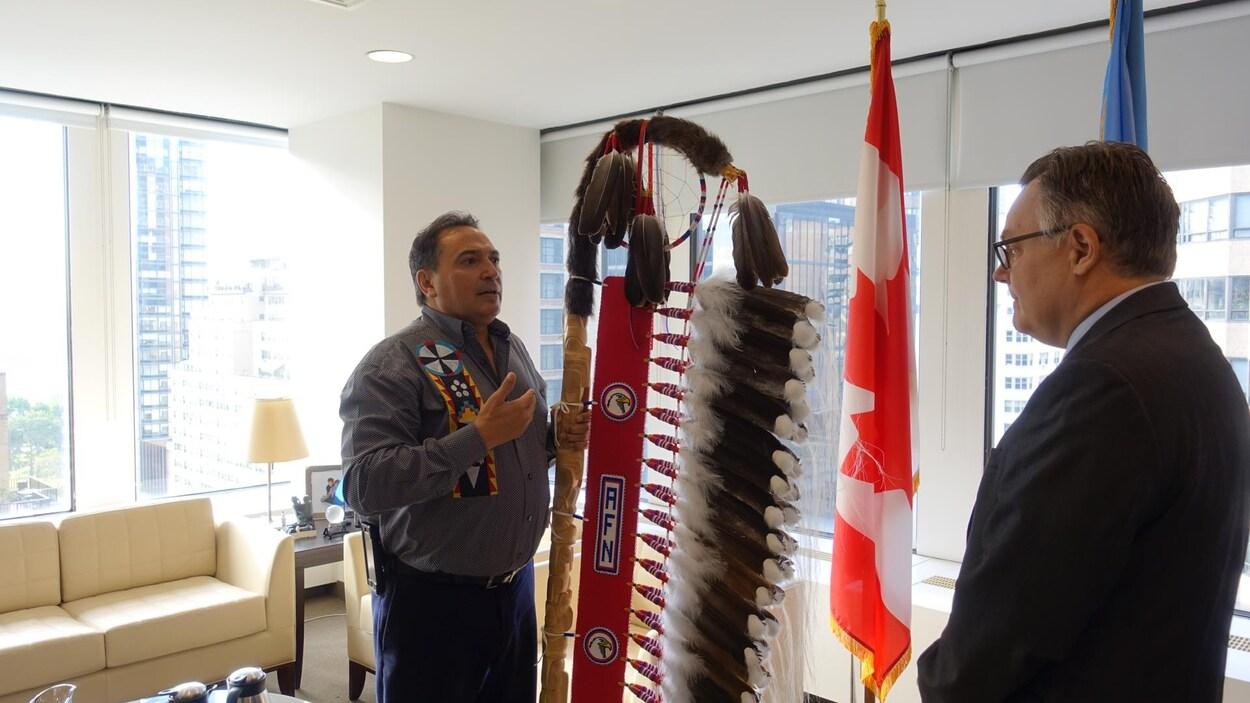 Le chef Perry Bellegarde (à gauche) offre le bâton à exploit à Son Excellence Marc-André Blanchard (à droite). Le bâton qui se courbe au-dessus comporte plusieurs ailes et porte une inscription de l'Assemblée des Premières Nations.