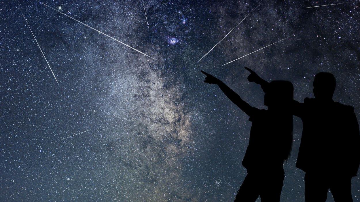 Deux humains regardent une pluie d'étoiles filantes.