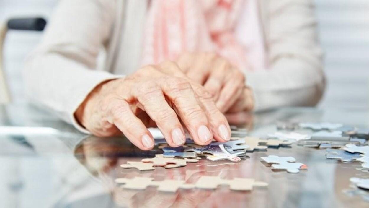 Gros plan sur la main d'une personne âgée qui joue à un casse-tête.