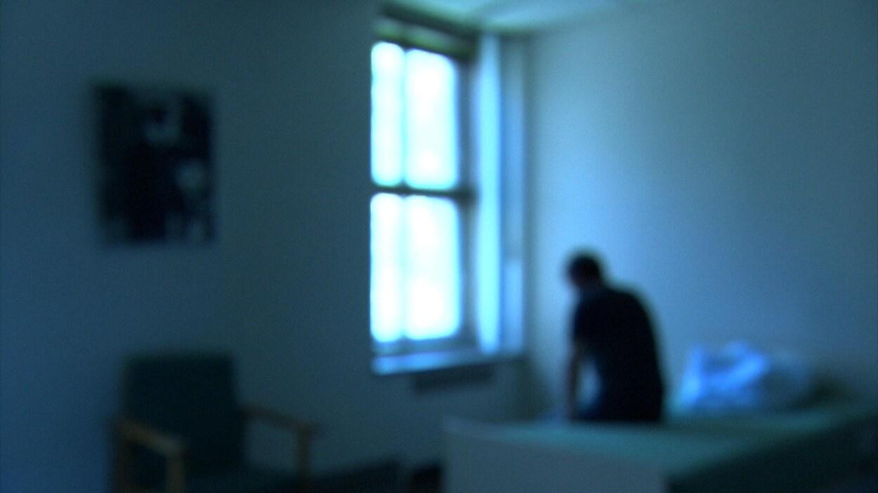 Une personne assise sur un lit qui semble triste.