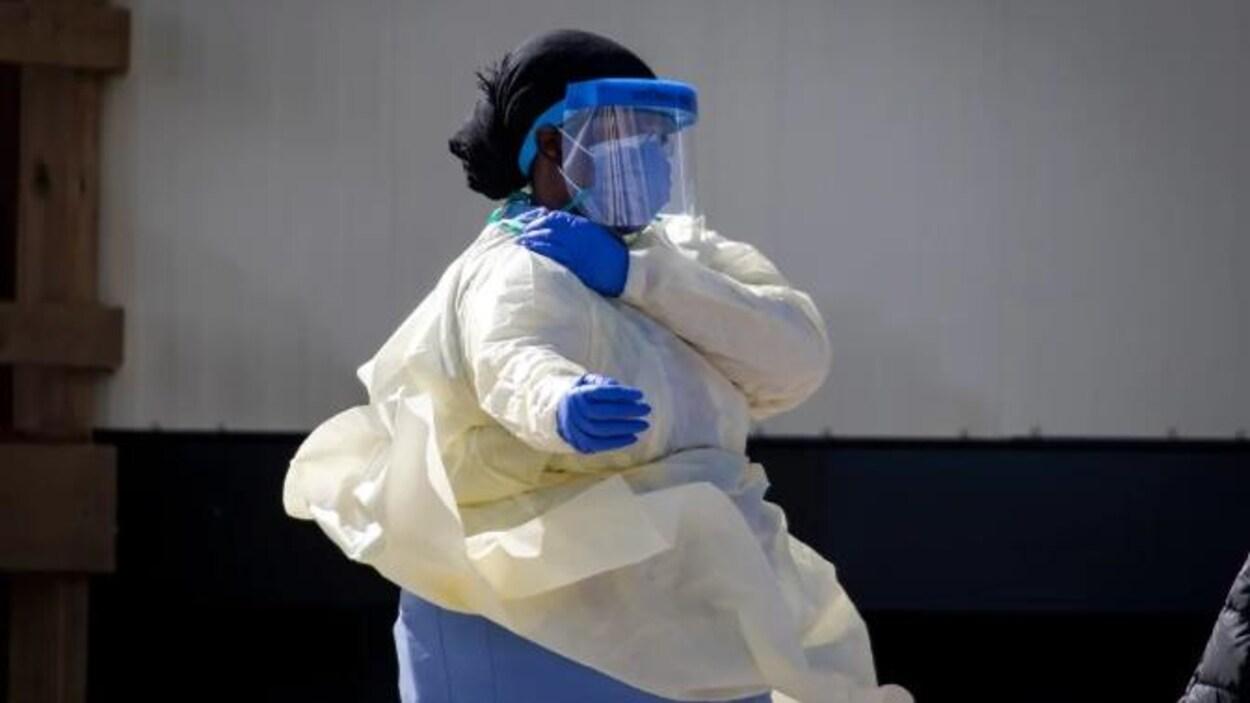 Une infirmière vêtue d'un équipement de protection personnelle.