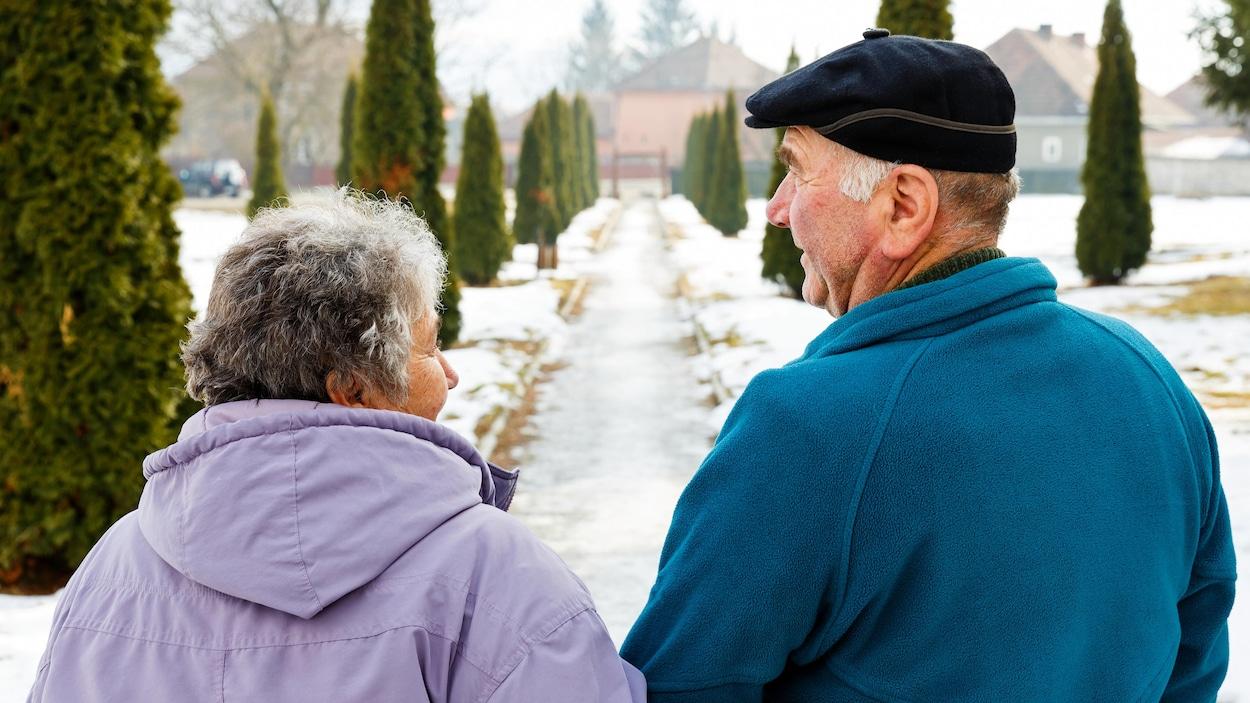 Un couple de personnes âgées marchant dans un sentier enneigé.