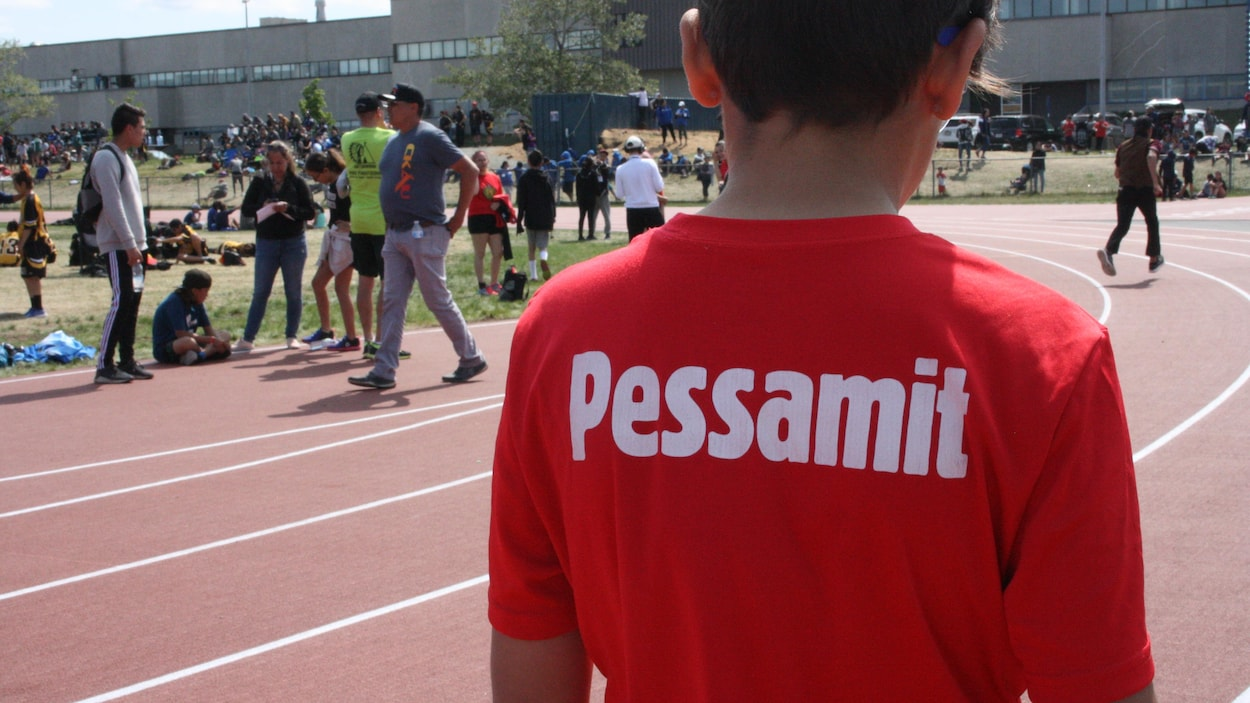Le mot Pessamit est inscrit sur le t-shirt rouge d'un jeune athlète qui se tient, avec plusieurs autres personnes au loin, sur une piste d'athlétisme.