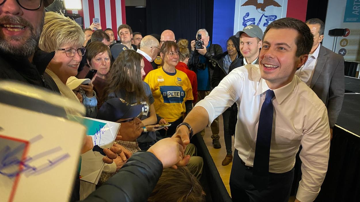 Un politicien serre la main de ses partisans.