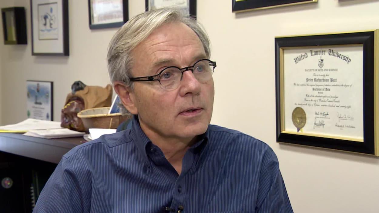 Peter Butt répond aux questions du journaliste, assis dans son bureau.