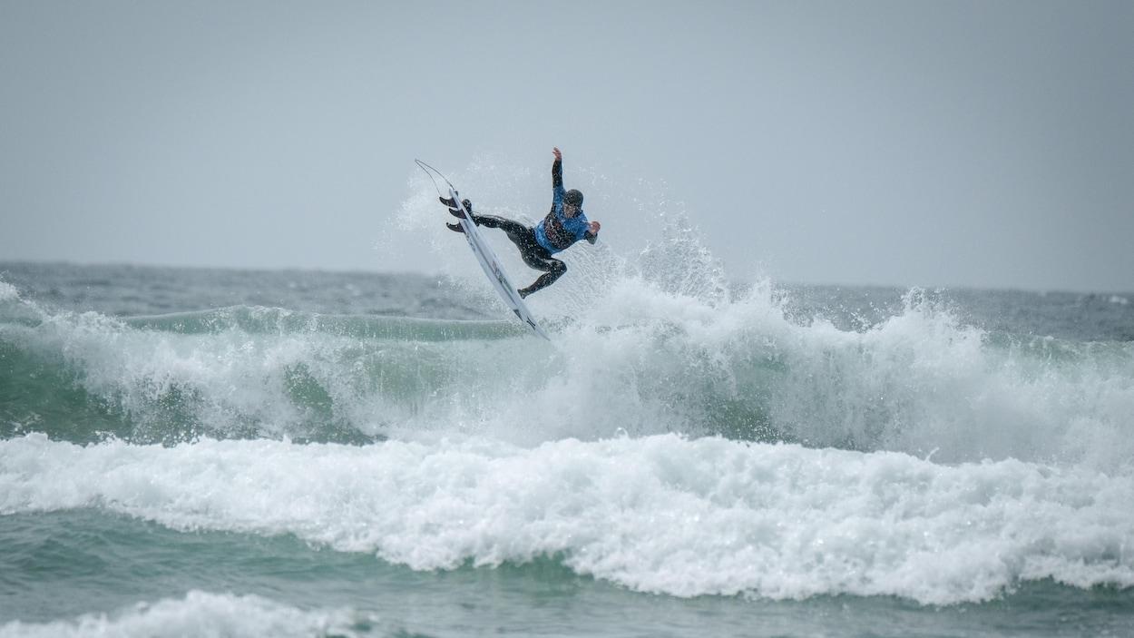 Peter Devries, champion canadien de surf 2019, est debout sur sa planche en haut d'une vague qui se brise à Tofino.