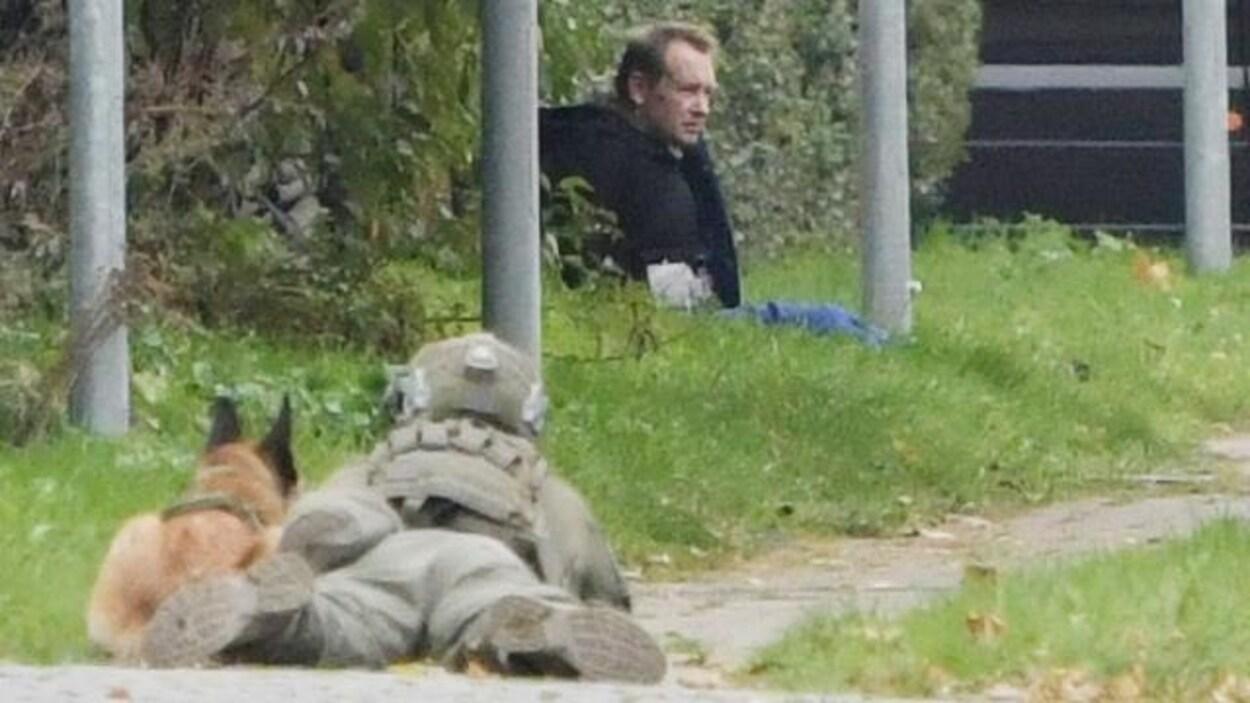 Un policier en uniforme couché au sol surveille Peter Madsen, assis près d'une rangée d'arbres.