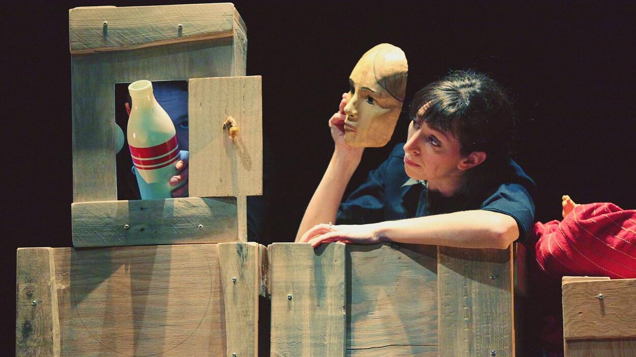 Une comédienne tient un masque dans une pièce de théâtre.