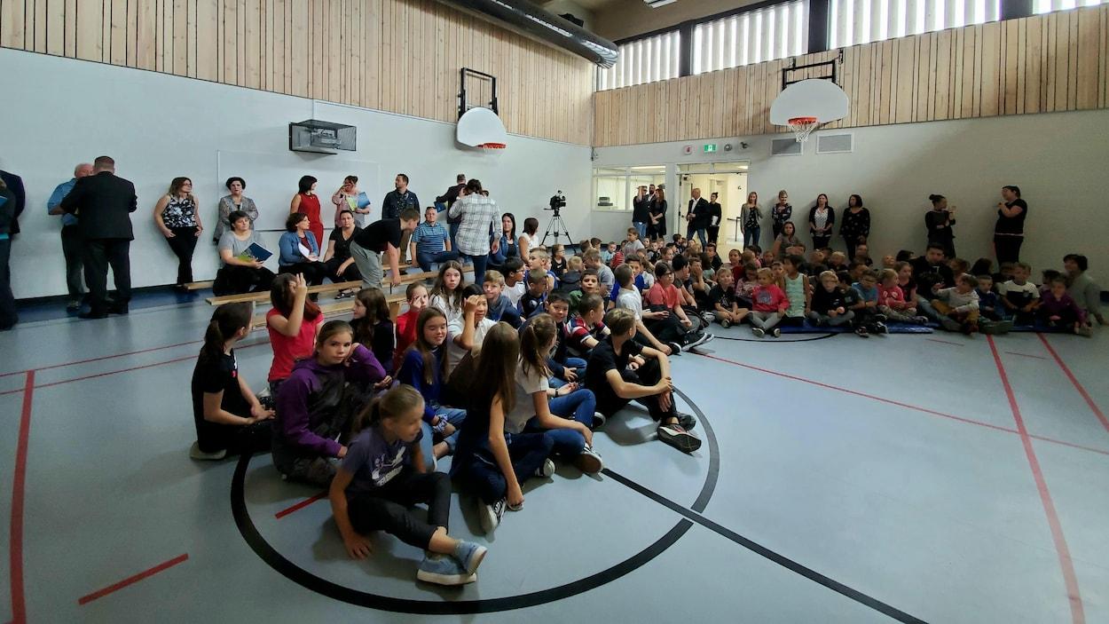Des enfants et des adultes dans un gymnase.