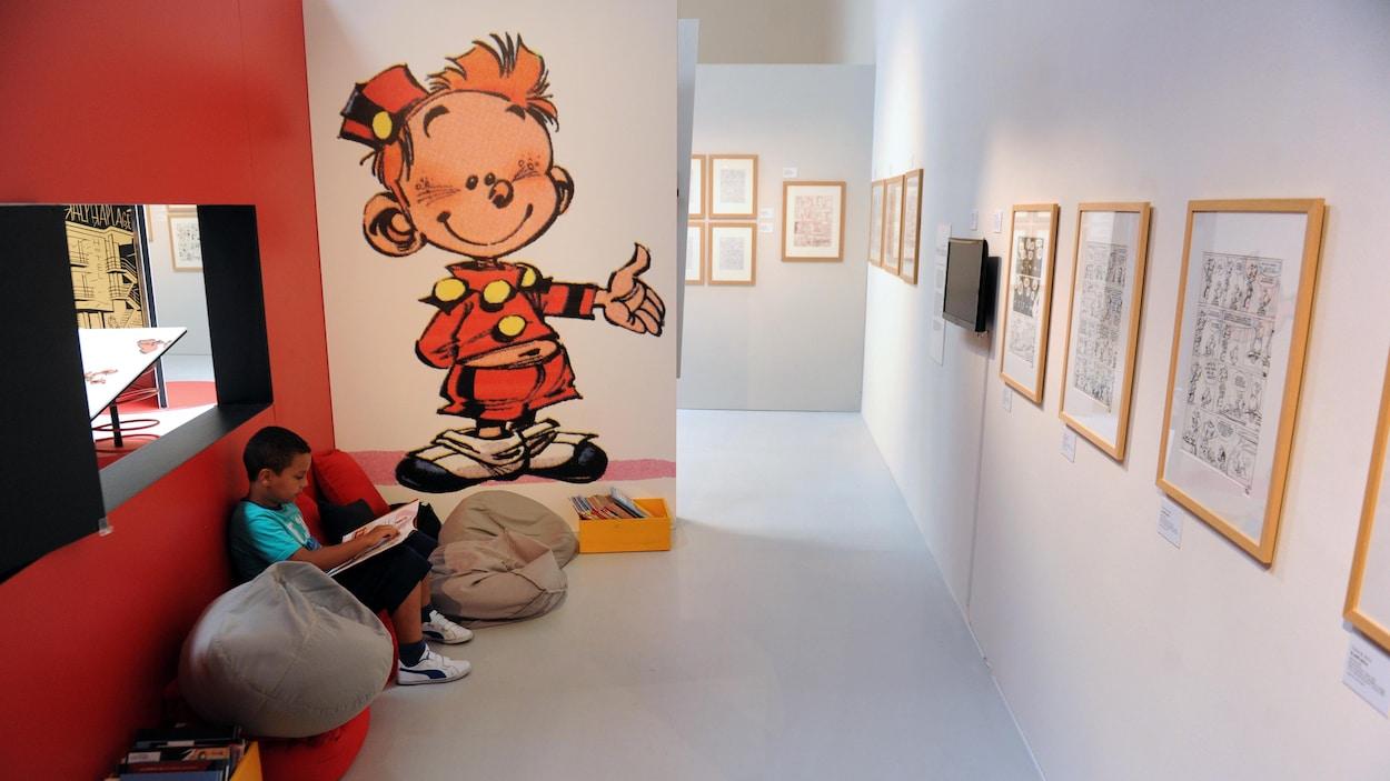 Un enfant lit une bande dessinée du Petit Spirou devant une affiche du personnage.
