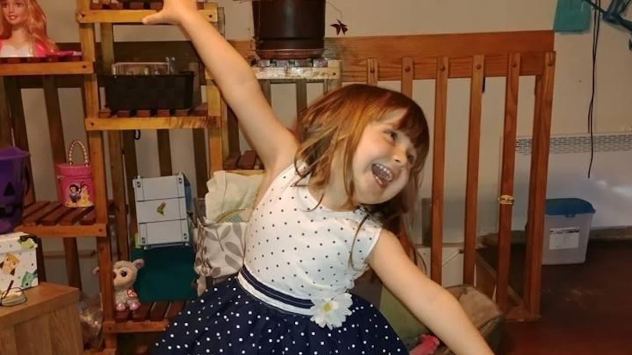 Une petite fille en robe sourit pour la caméra.