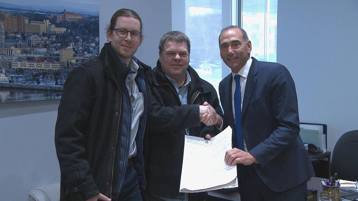 Marc-André Galbrand, Rémi Aubin et Richard Martel montrent la pétition.