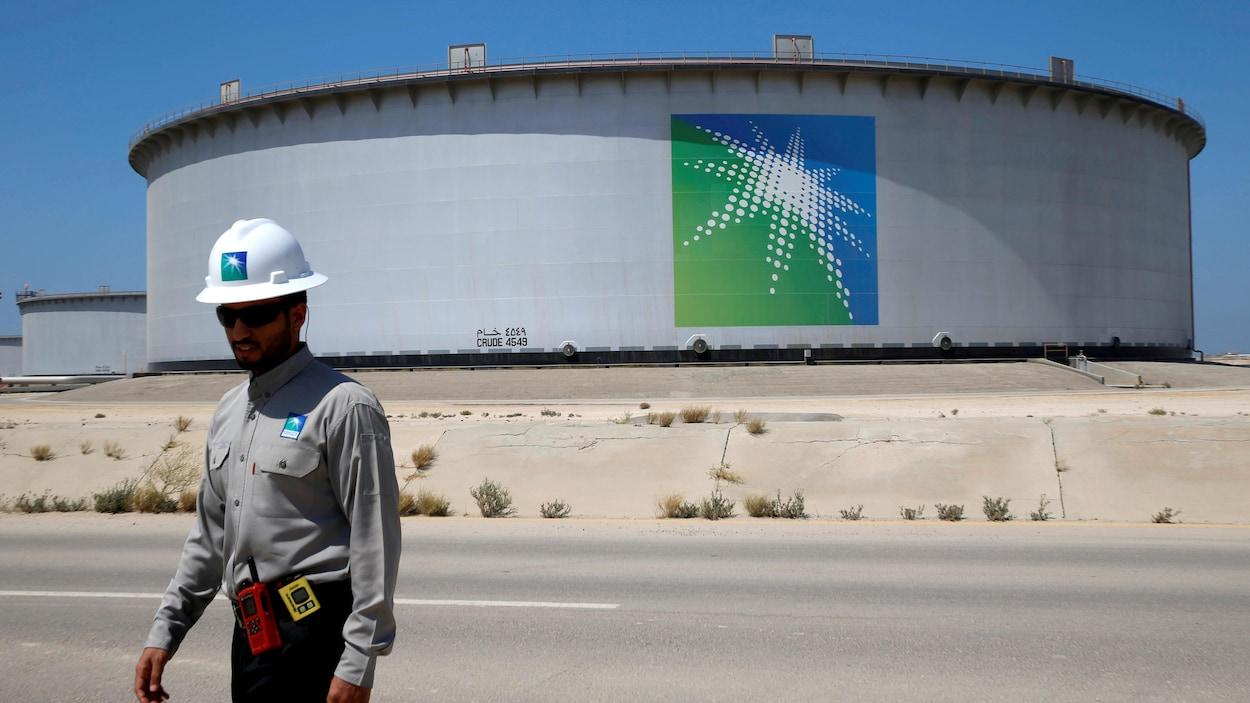 Un employé d'une compagnie pétrolière devant un réservoir.