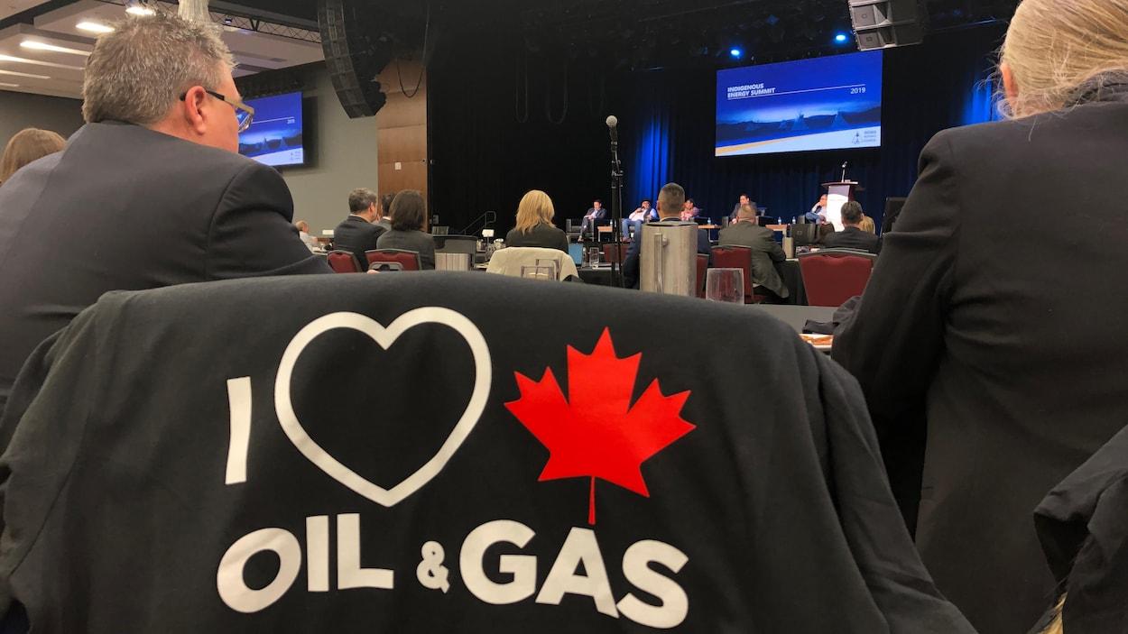 Des participants au Sommet autochtone sur l'énergie écoutent les membres d'un panel discuter sur scène des enjeux énergétiques.