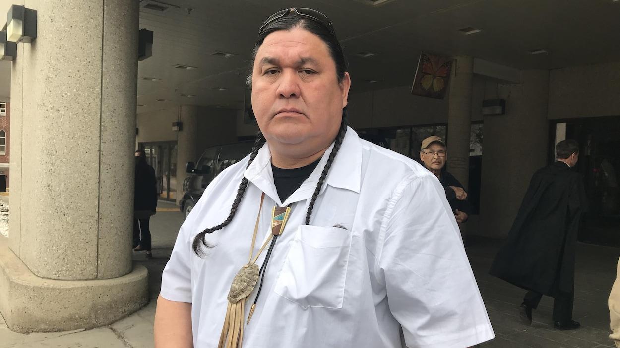 Un homme porte un t-shirt blanc. Il a de longues tresses et tient dans sa main une plume d'aigle.