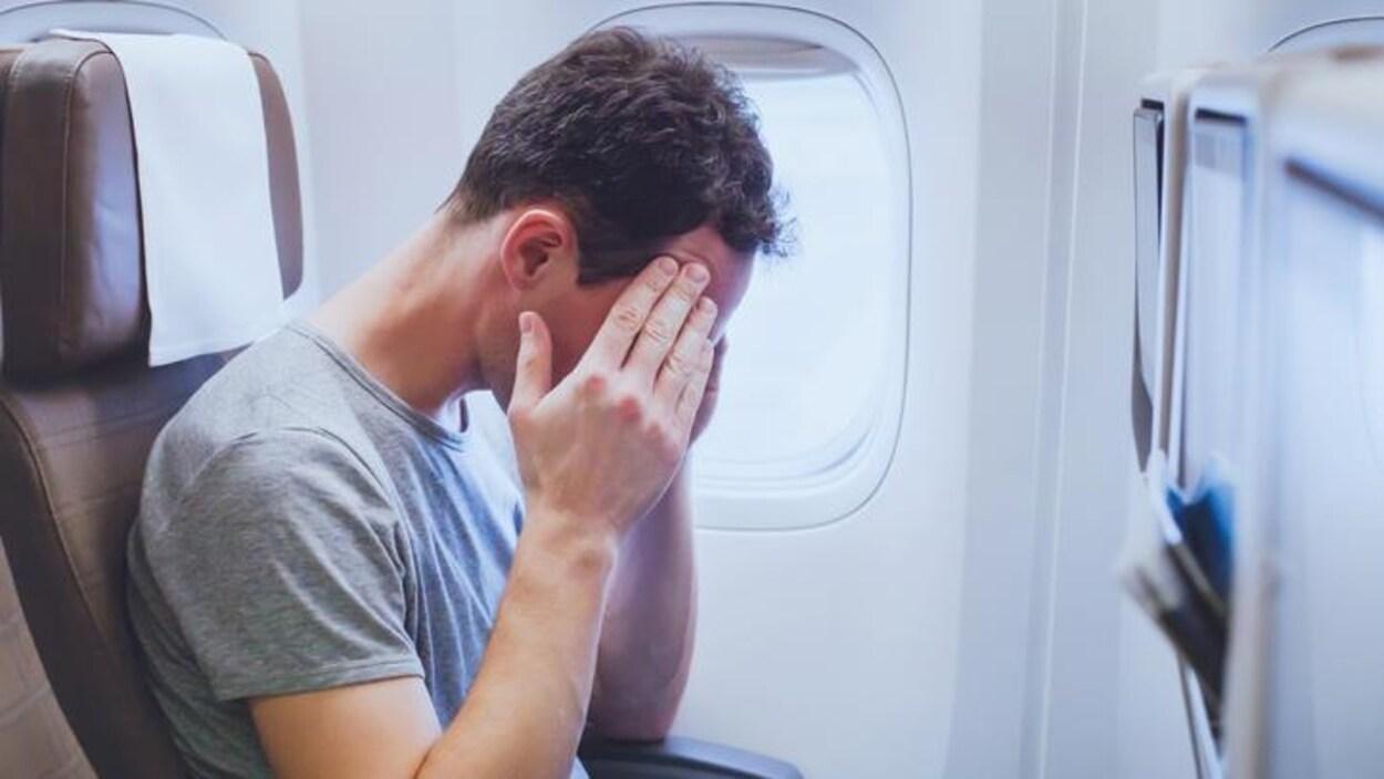 Un homme assis la tête entre les mains dans un avion.