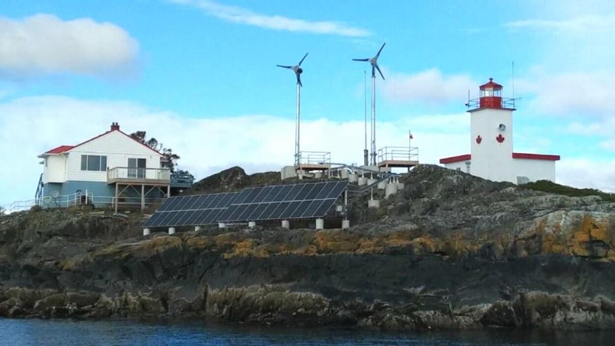 Deux éoliennes surplombent l'île rocailleuse. À leurs pieds se trouvent des panneaux solaires, le phare et la maison du gardien.