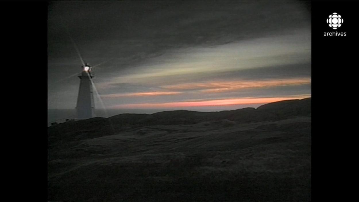 Un phare brille dans la nuit sur un paysage côtier de Terre-Neuve.