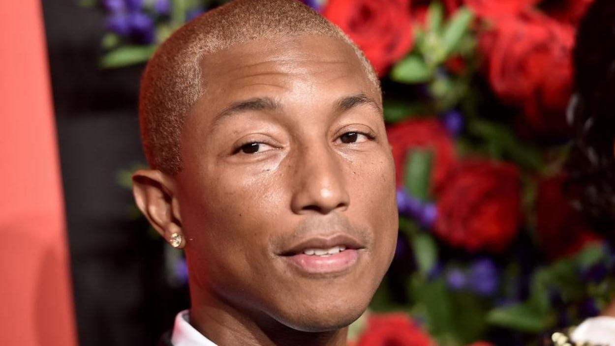 Gros plan sur Pharrell Williams avec des roses rouges en fond.