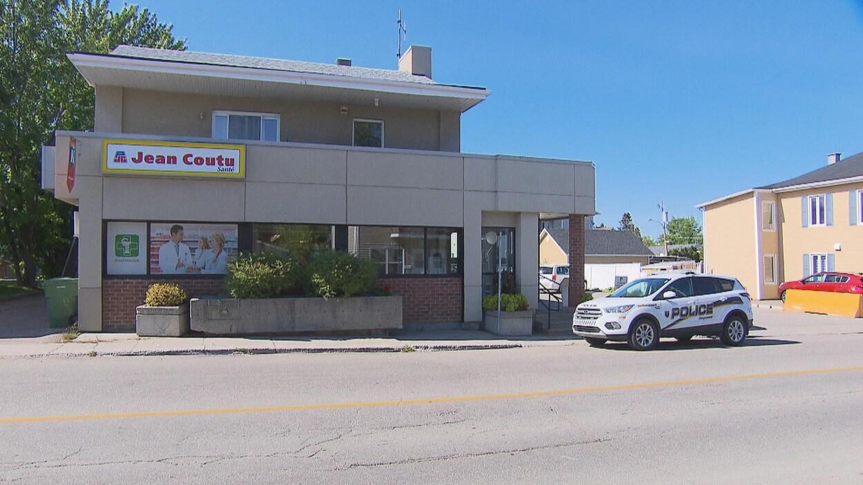 Un véhicule de police est garé devant une pharmacie.