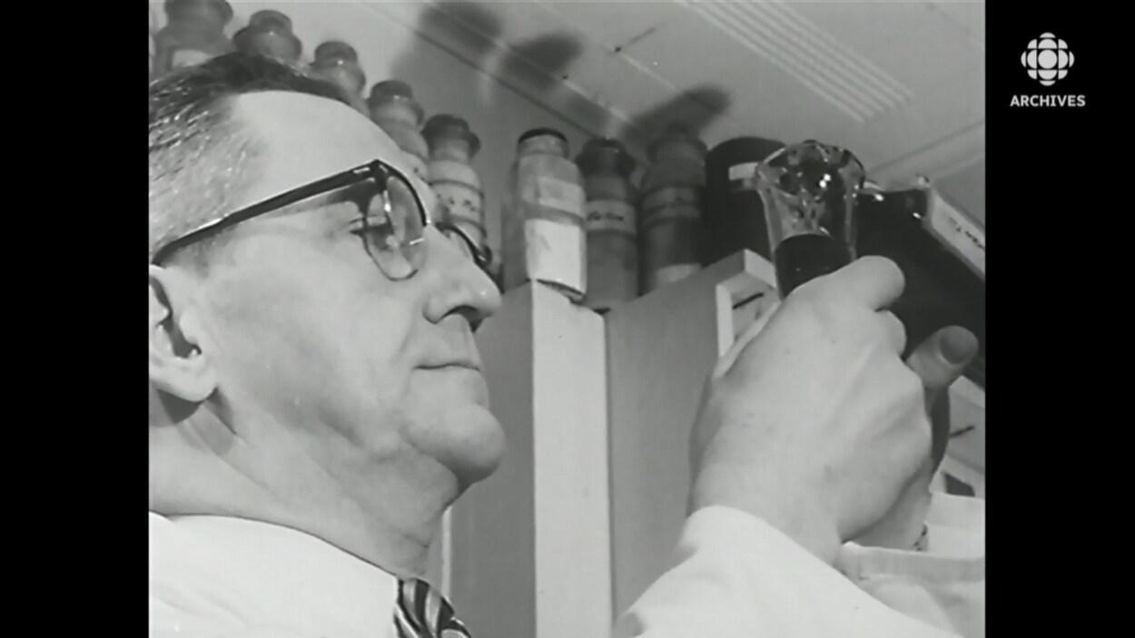 Un pharmacien mesure une dose d'un flacon de médicaments.