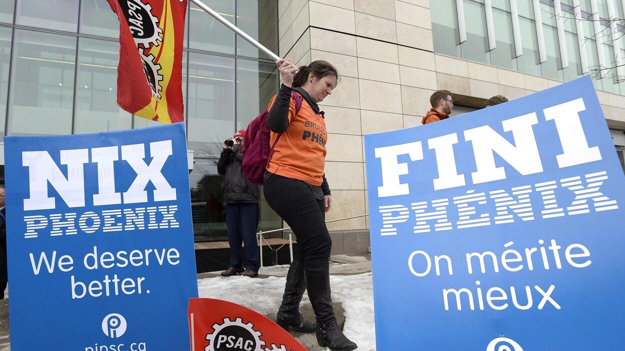 Des fonctionnaires ont participé à un rassemblement contre le système de paye Phénix à l'extérieur des bureaux du Conseil du Trésor du Canada, à Ottawa, le 28 février 2018.