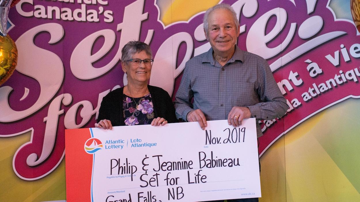 Jeannine et Philip Babineau tiennent un chèque géant sur lequel il est écrit « Philip & Jeannine Babineau Set for Life Grand Falls, NB ».