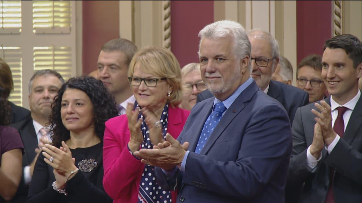 Philippe Couillard entouré des membres de son gouvernement lors de la cérémonie d'assermentation des ministres au Salon rouge de l'Assemblée nationale.