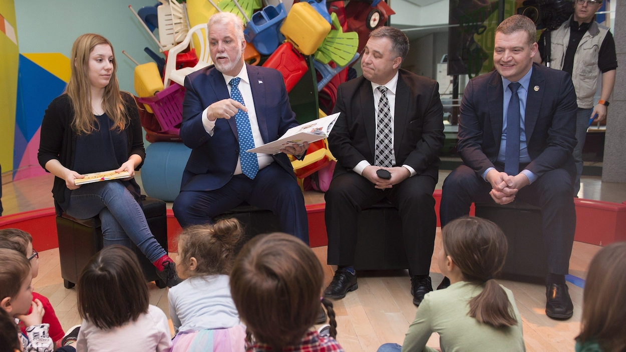 Le premier ministre Philippe Couillard et les ministres de l'Éducation, Sébastien Proulx, et de la Famille, Luc Fortin, sont assis devant des enfants.