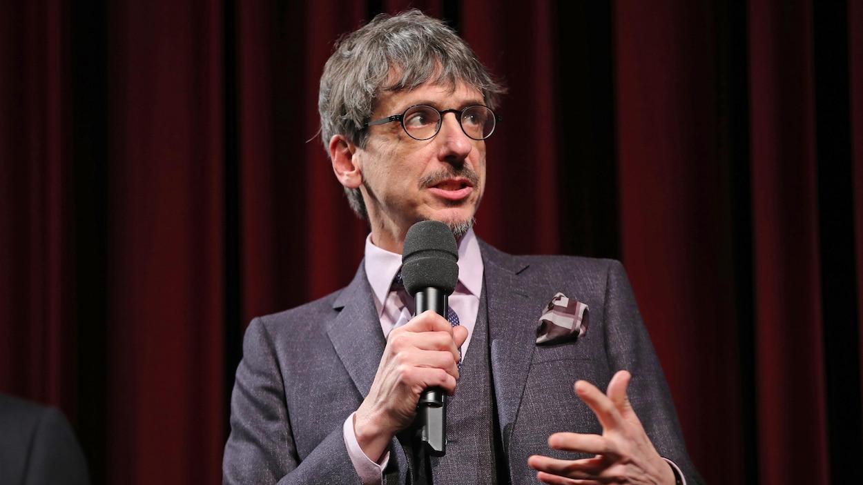 L'homme porte des lunettes et parle dans un micro.