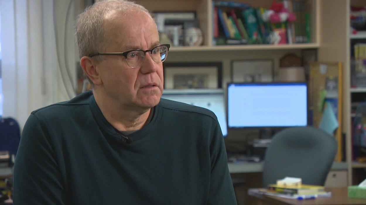 L'enseignant Philippe Habeck porte des lunettes et se trouve dans une salle de classe.