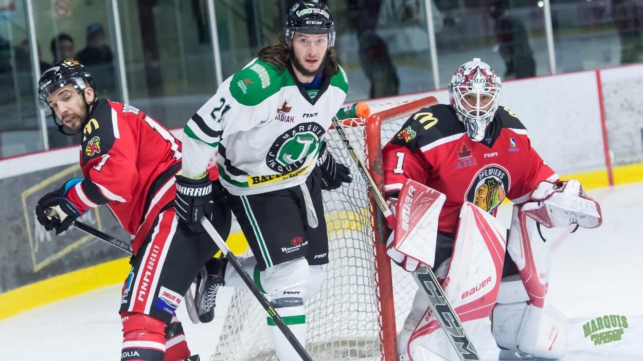 Des joueurs de hockey se trouvent derrière un filet qui est étroitement surveillé par un gardien de but.