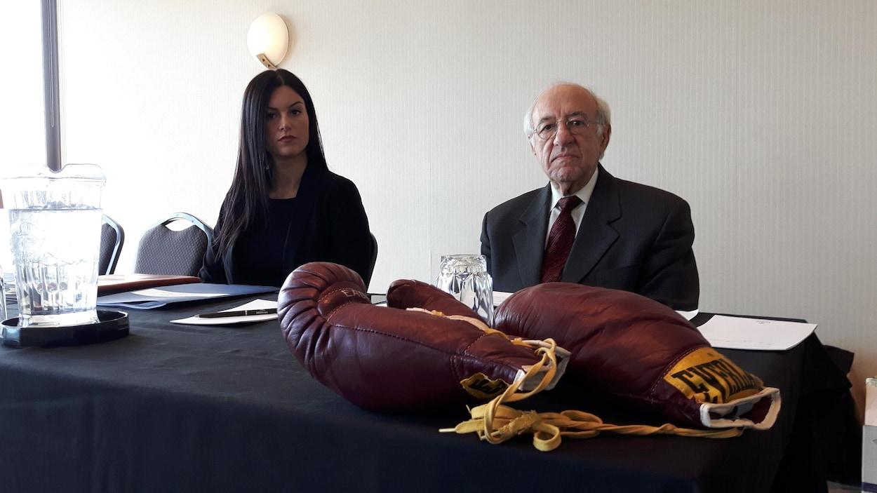 Philippe Sauvageau et son avocate sont assis derrière une table en attendant le début d'une conférence de presse. Une paire de gants de boxe est déposée sur la table.