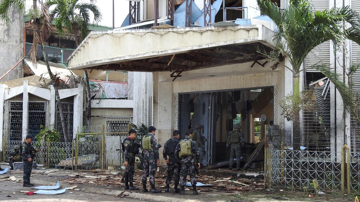 Des militaires sont debout dans les débris à l'entrée d'une église dont les portes ont été détruites lors de l'explosion d'une bombe.