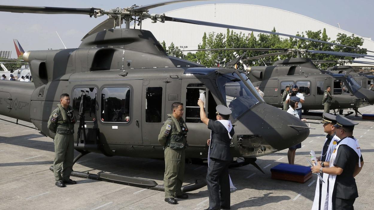 Un aumônier militaire philippin asperge d'eau bénite, en 2015, un des huit appareils alors acquis de Bell Helicopter