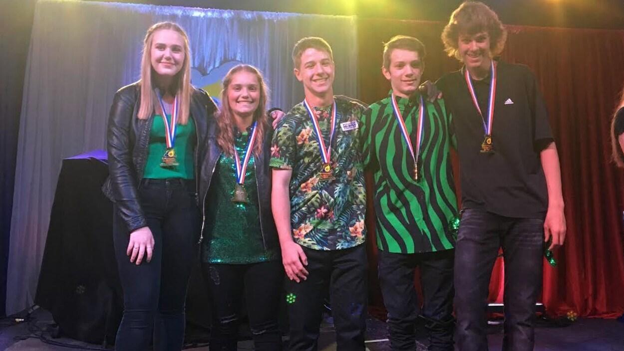 Cinq gagnants et leur médaille sur la scène.