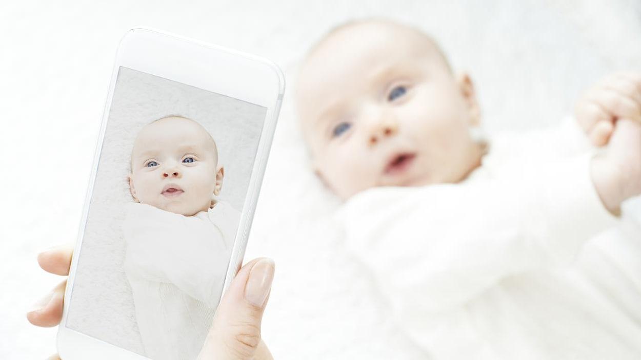 Une mère prend en photo son poupon avec son téléphone cellulaire.
