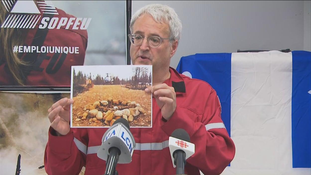 Pierre Dufour tient une photo dans ses mains et montre le feu de camp qui aurait été mal éteint la semaine dernière.