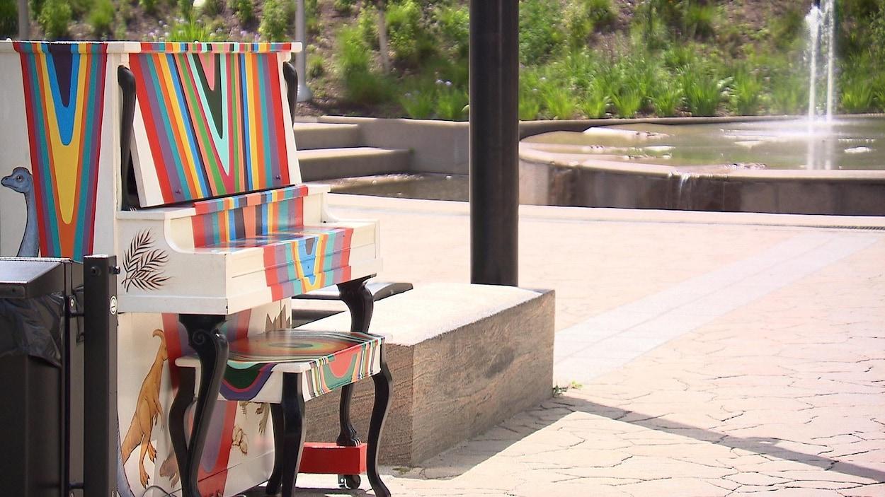Un piano droit multicolore devant une fontaine.