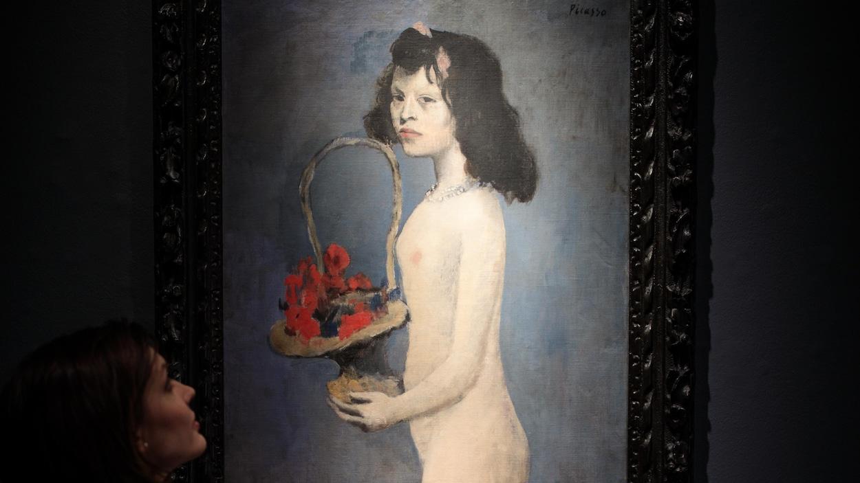 Une femme regarde le tableau de Pablo Picasso « Fillette à la corbeille fleurie », exposé à Londres, en février 2018.