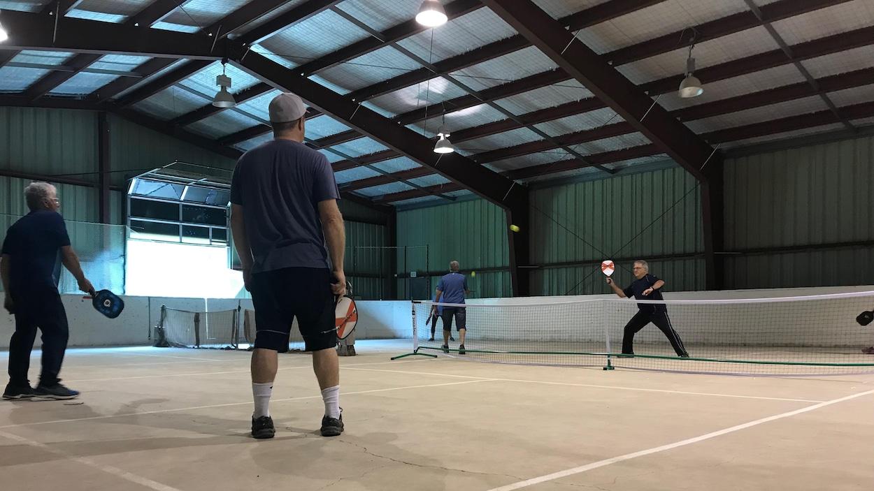 Des hommes jouent au pickleball dans un aréna converti en terrain sportif.