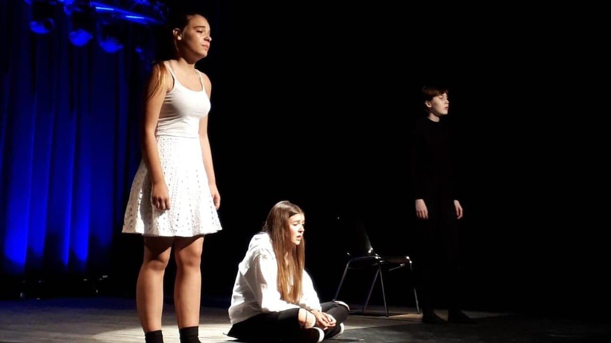 Trois jeunes jouent dans une pièce de théâtre