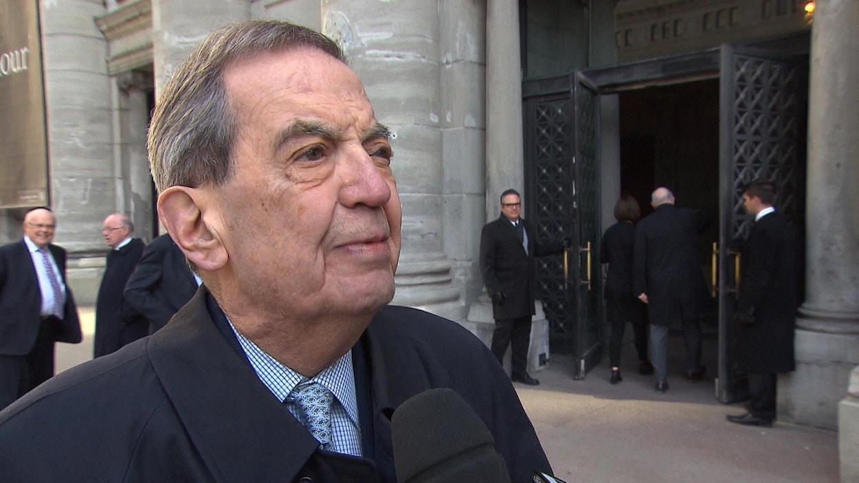 Pierre De Bané en entrevue, devant un grand bâtiment.