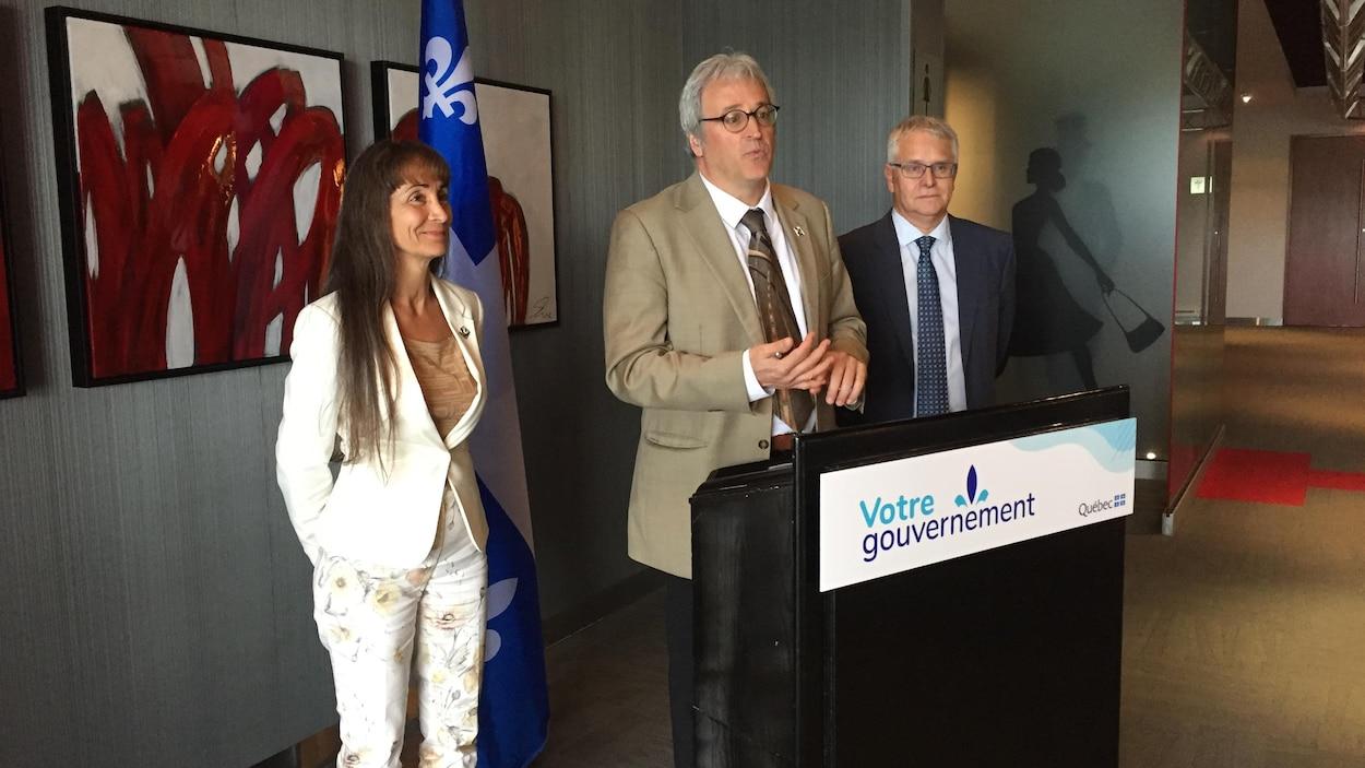 Pierre Dufour, encadré d'une femme et d'un homme, parle derrière un lutrin du gouvernement du Québec.
