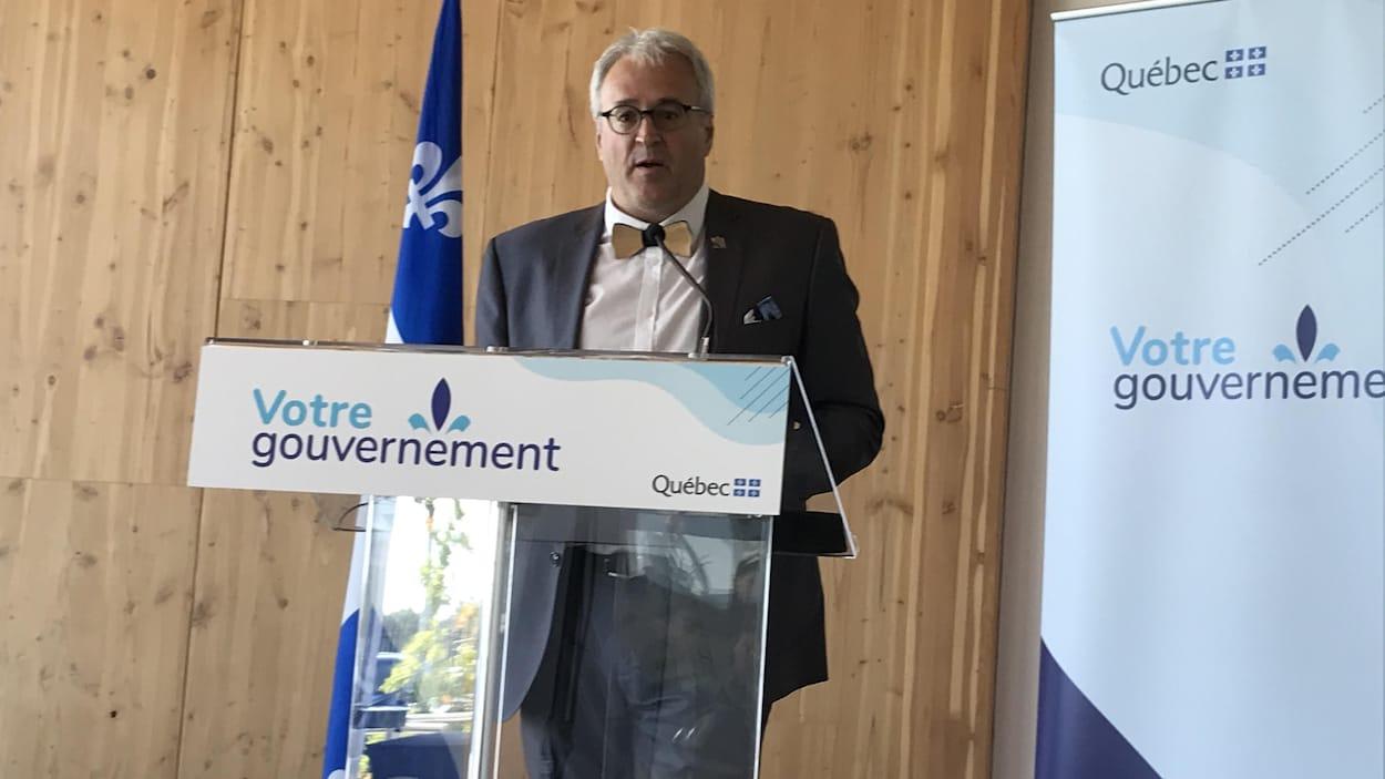 Pierre Dufour parle au micro derrière un lutrin du gouvernement du Québec.