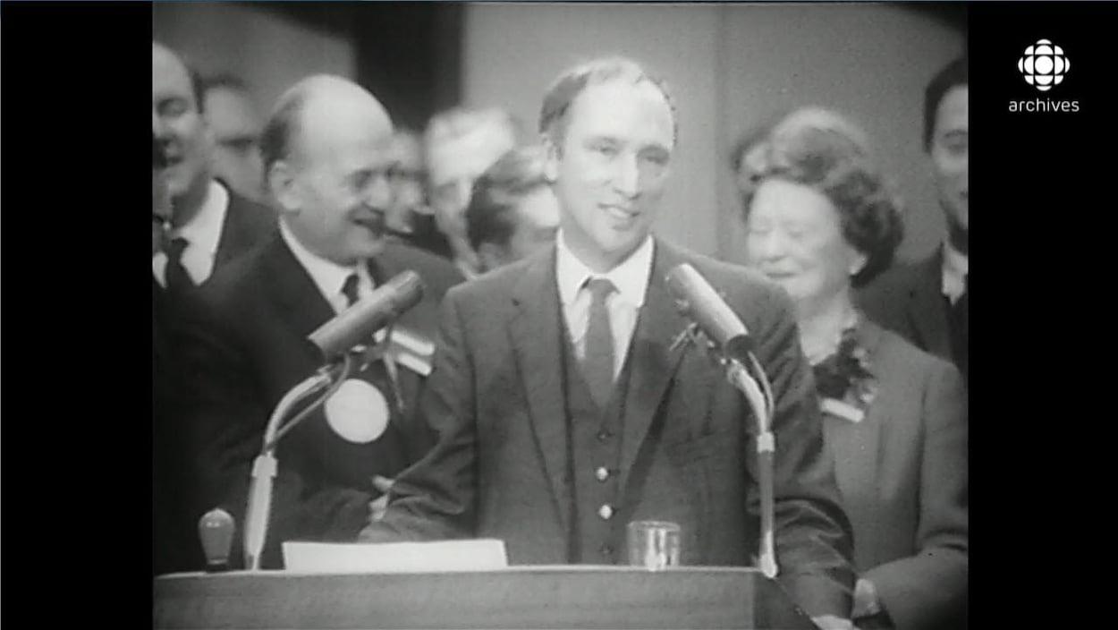 Pierre Elliott Trudeau, souriant et entouré de son équipe, marquant une pause dans son discours au lutrin.