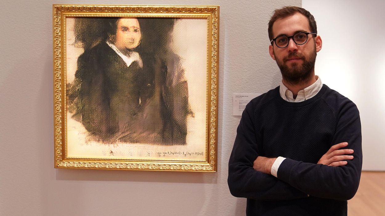 Pierre Fautrel pose, les bras croisés, à côté du tableau «Portrait d'Edmond de Belamy», accroché à un mur.