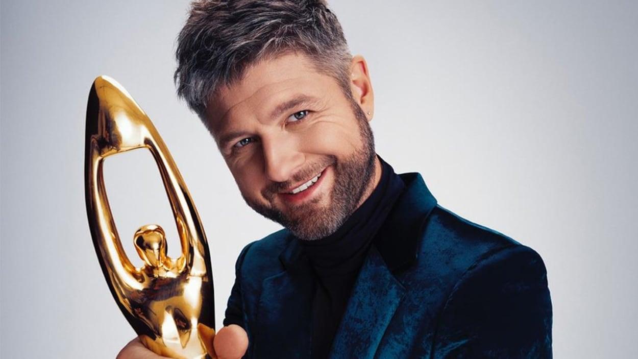 Un homme vêtu d'un veston en velours bleu tient un trophée Félix dans sa main droite.